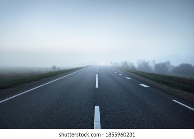 Panoramic view of the empty highway through the fields in a fog at night. Moonlight, clear sky. Sunrise. Europe. Transportation, logistics, travel, road trip, freedom, driving. Rural scene