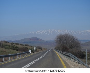 Panoramic view of an empty road in the Israeli Golan Heights and Mount Hermon with snowy peak in the distance