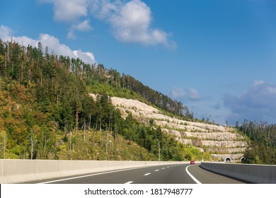 Panoramic view of entrance of tunnel in the mountains of Croatia. Beautiful landscape with mountain and forest, highway with red car