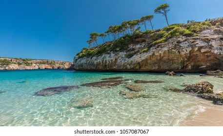 Panoramic view of Es calo des Moro beautiful beach. Pine trees shadows on the crystalline water. Classified as one of the world best beaches. Located in Santanyi, Majorca, Balearic Islands, Spain