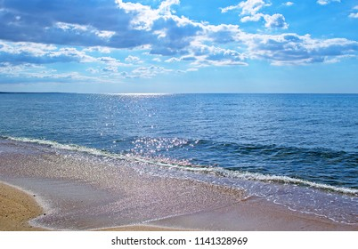 Panoramic view of evening sea with empty beach & sun glares in shining waves. Black Sea, Feodosia.