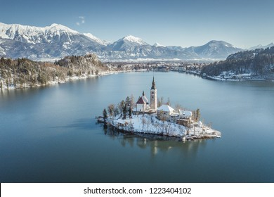Panoramic view of famous Bled Island (Blejski otok) at scenic Lake Bled with Bled Castle (Blejski grad) and Julian Alps in the background on a beautiful sunny day in winter, Slovenia