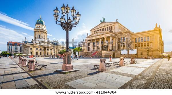 Panoramasicht auf den berühmten Gendarmenmarkt mit Berliner Konzerthalle und Deutscher Kathedrale bei goldenem Abendlicht bei Sonnenuntergang mit blauem Himmel und Wolken im Sommer, Berlin Mitte, Deutschland