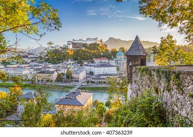 Panoramic view of the famous historic city of Salzburg with Hohensalzburg Fortress and Salzach river in beautiful golden evening light at sunset with blue sky and clouds, Salzburger Land, Austria