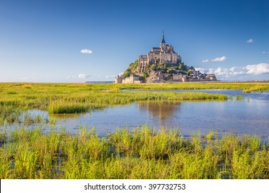 Panoramic view of famous historic Le Mont Saint-Michel tidal island on a sunny day with blue sky and clouds in summer, Normandy, northern France