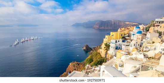 Panoramic view of famous Santorini island. The famous town of Oia in the morning. A line of sailing yachts at sea. Good vacation. Oia, Santorini, Greece