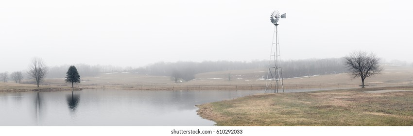 Panoramic view of farmland and pond shrouded in fog on an early spring morning