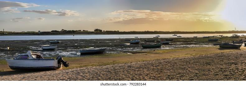 Panoramic view of fishing boats ashore with low tide in El Rompido, Huelva, Spain.