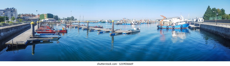 Panoramic view of fishing boats moored on the dock of Vilanova de Arousa harbor