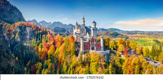 Panoramic view from flying drone of Neuschwanstein Castle, 19th-century hilltop fairytale castle. Exciting morning scene of Bavaria. Magnificent landscape of Alps, Germany, Europe.