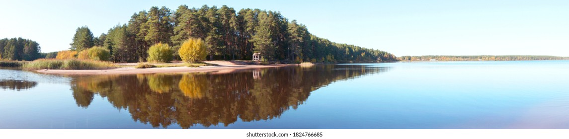 Panoramic view of the forest island, pond or lake. The reflection in the water. Beautiful widescreen autumn landscape.