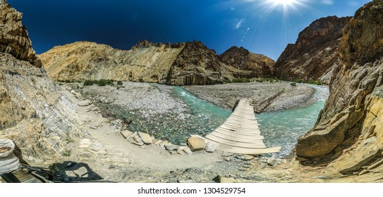 Panoramic view of fragile wooden footbridge croosing beautiful icy river in Ladakh, India.