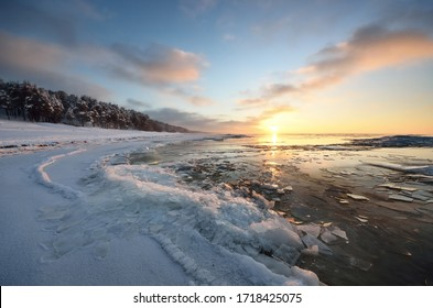 Panoramic view of the frozen Baltic sea shore at sunset. Ice fragments close-up, snow-covered coniferous forest in the background. Colorful cloudscape. Symmetry reflections on the water. Latvia