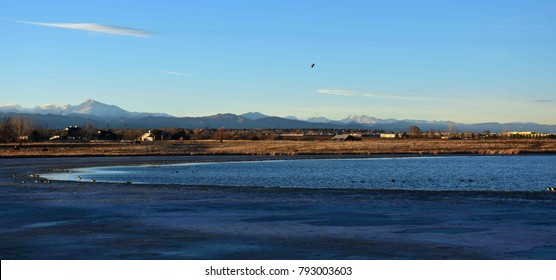 panoramic view of  frozen stearns lake,  canada geese, and mountains, at the carolyn holmberg preserve at rock creek farm,  in broomfield, colorado