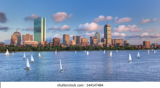 A panoramic view of the full Boston skyline with the Charles River full of sailboats as sunset approaches