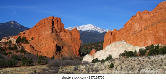 Panoramic view of Garden of the Gods in Colorado Springs - red sandstone formations with Pikes Peak in background.