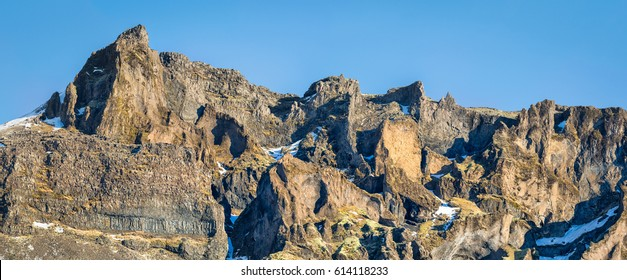 a panoramic view of the geological structures within the multiple lava flow layers of the mountains behind Hof in South East Iceland.  A  jointed Basalt sill dominates the lower left series of flows.