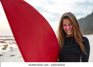Panoramic view of glad smiling attractive surfer has pink zinc cream applied on face for sun rays protection, has long wavy hair, feels happy to buy new board, poses for popular travel magazine
