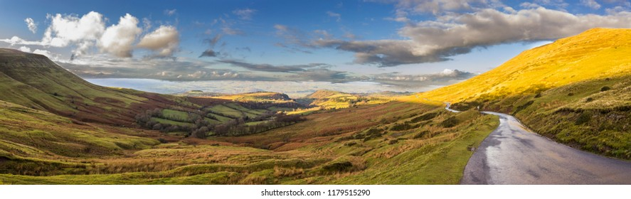 A panoramic view from Gospel Pass at Black Mountains during sunset with incredible views of Wales countryside, grass, road