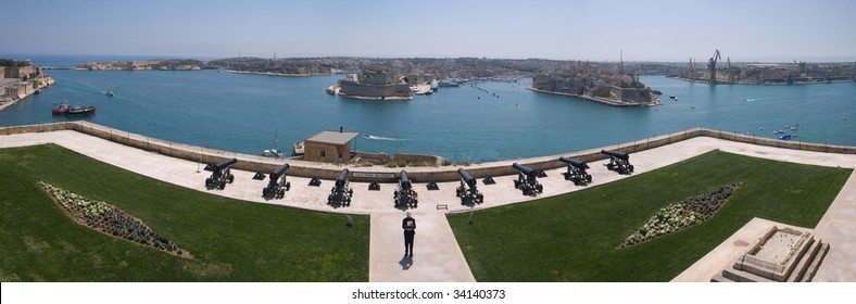 Panoramic view of the Grand Harbour, Valletta, from the Upper Barrakka Gardens with Saluting Battery in Foreground and an reenactment actor giving a speech before a demonstration of a battery Salute.