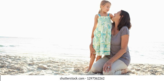 Panoramic view of grandmother and grand daughter enjoying sunny sky beach holiday together, hugging smiling on sand, outdoors. Senior and child love fun bonding family travel activities lifestyle.