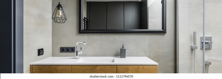 Panoramic view of gray bathroom with modern countertop basin, mirror and shower