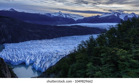 Panoramic view of the Gray Glacier, located inside Torres del Paine National Park. There are some trees on the right and large snowy mountains in the background. Sunset sky in autumn.