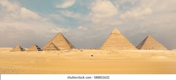 Panoramic view of Great Egyptian pyramids in Giza Plateau: famous pyramid of Cheops, Chephren, Mykerinos and three step pyramids. Museum complex Giza near Cairo in Egypt, wide shot.