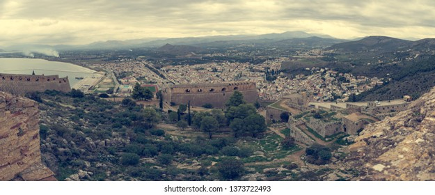 Panoramic view of greek coastal town with ancient ruins.