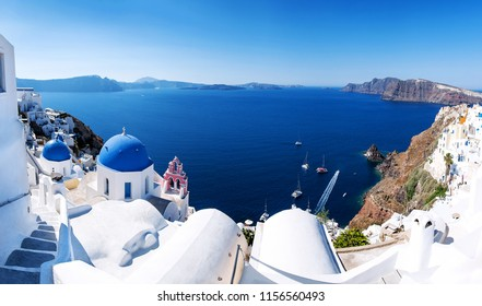 Panoramic view with Greek orthodox church with blue domes and sea in Oia in Santorini, Greece, Europe. Beautiful scenery above the caldera overlooking the Aegean Sea.
