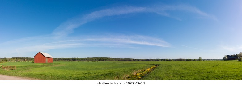 Panoramic view of a green field with red barn and ditch with yellow flowers on sunny spring day in Vantaa Finland