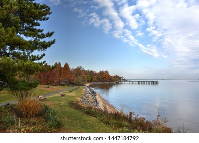 Panoramic view of a green grass bluff overlooking the shoreline along the Chesapeake Bay. The coast leads to a fishing pier extending out into the water from a colorful, autumn tree lined peninsula.