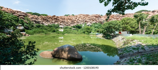 Panoramic view of a green pond against a backdrop of boulders