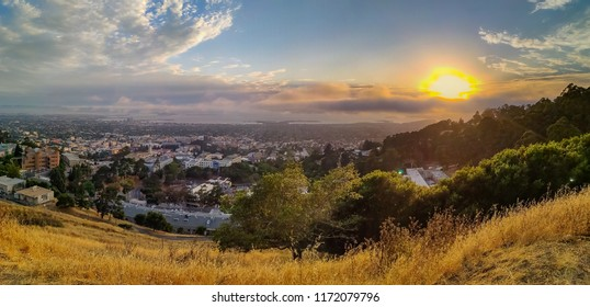 Panoramic view from Grizzly Peak in Berkeley Hills onto Berkley, Oakland and San Francisco with Karl the fog enveloping the city at sunset