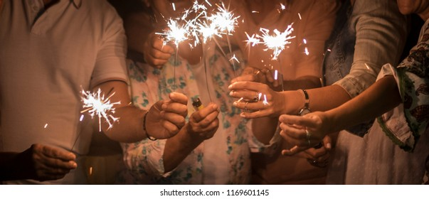 panoramic view of group of friends mixed ages celebrate together in the night with sparkles file light. new year eve or birthday or christmas event to live friednship and family with happiness