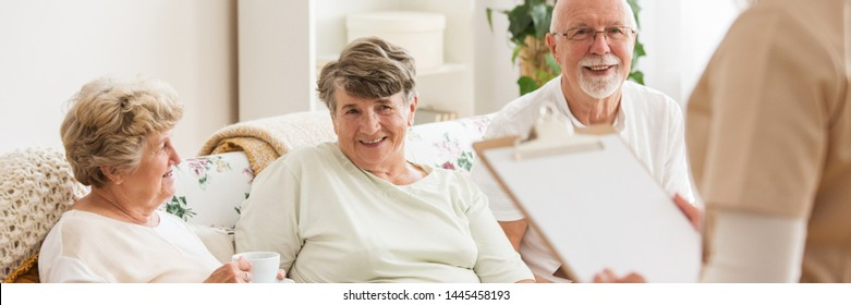 Panoramic view of happy seniors sitting on a couch in care center and looking at their nurse