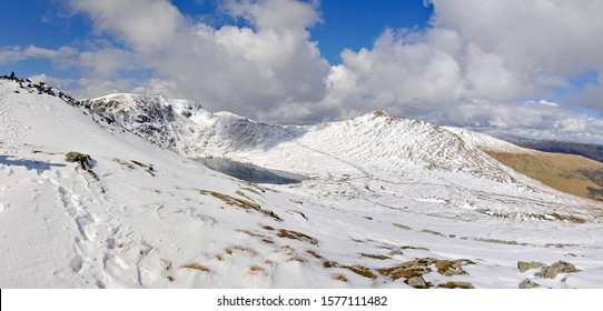 Panoramic view of the Helvellyn horseshoe (Lake District, Cumbria, England) on a clear winter's day. A walker is visible on the left approaching Striding Edge.