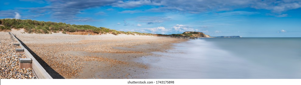 Panoramic view of Hengistbury Head beach, Dorset with groyne in the foreground and Isle of Wright Needles in background