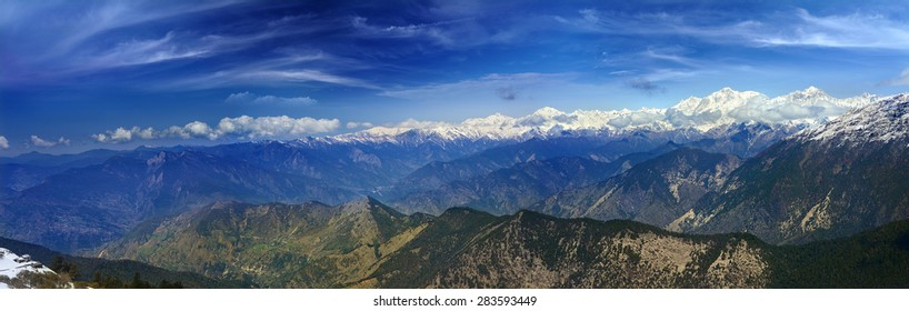 panoramic view of the high glacier capped mountains and forested mountains in the Himalayas, Chopta, Uttarakhand, India