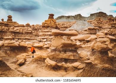 Panoramic view of hiker in red jacket standing in Goblin Valley State Park amidst beautiful hoodoos sandstone formations, Utah, USA