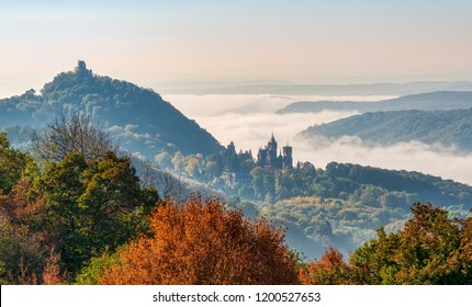 Panoramic view of the hill Drachenfels with the castle ruin and the castle Drachenburg in Siebengebirge, morning fog arose from the river Rhine valley, Königswinter, North Rhine-Westphalia, Germany
