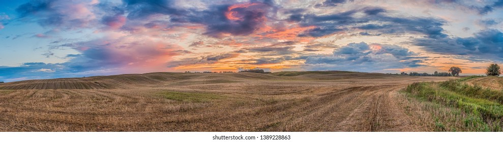 Panoramic view of the hills and fields after mowing the grain during the summer sunset. Warmia and Masuria. Poland