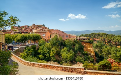 Panoramic view of hilltop medieval ocher village of Roussillon, one of the most beautiful villages of France, in a sunny summer day. Provence, Vaucluse, travel France.