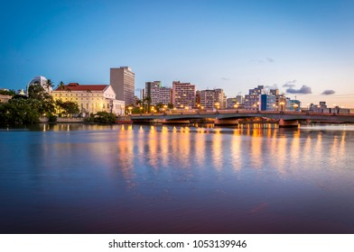 Panoramic view of the historic architecture of Recife in Pernambuco, Brazil at sunset showcasing one of its famous bridges over the Capibaribe river and buildings at downtown.