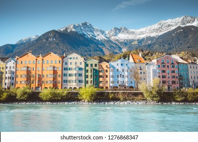 Panoramic view of the historic city center of Innsbruck with colorful houses along Inn river and famous Austrian mountain summits in the background in beautiful evening light at sunset, Tyrol, Austria