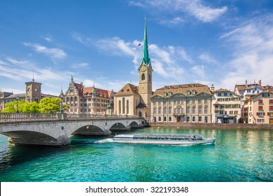 Panoramic view of the historic city center of Zurich with famous Fraumunster Church and excursion boat on river Limmat on a sunny day with blue sky, Canton of Zurich, Switzerland