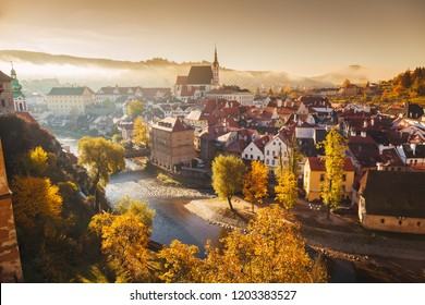 Panoramic view of the historic city of Cesky Krumlov with famous Cesky Krumlov Castle, a UNESCO World Heritage Site since 1992, in beautiful golden morning light at sunrise in fall, Czech Republic