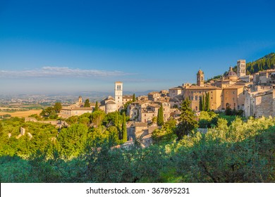 Panoramic view of the historic town of Assisi in beautiful golden morning light at sunrise with blue sky and clouds in summer, Umbria, Italy