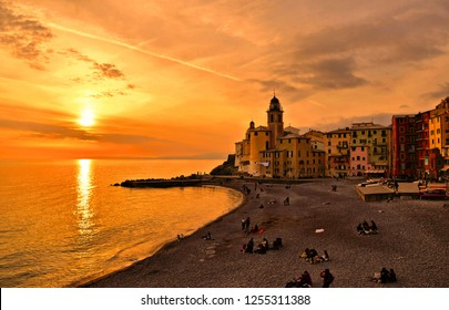 Panoramic view of historical Old Town Camogli and sand beach with people on sunset in mediterranean coast in Camogli, italian Riviera, Italy
