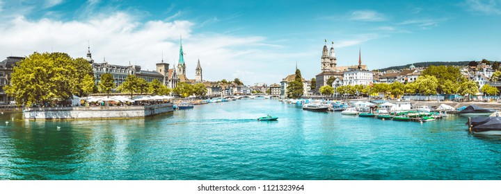 Panoramic view of historical Zurich city center with churches in the background and boats on beautiful river Limmat on a sunny day with blue sky and clouds in summer, Canton of Zurich, Switzerland